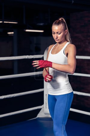 Boxing woman binds the bandage on hand