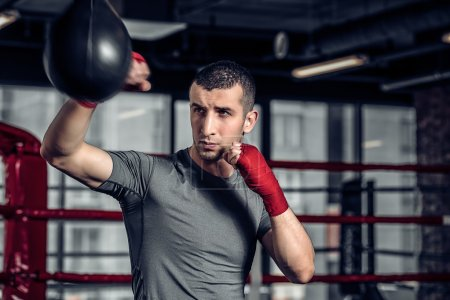 Male boxer using a punching bag in gym