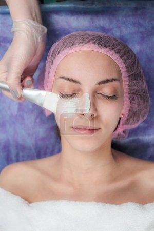 Facial mask applying using brush in Beauty salon