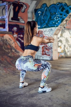 Athletic young woman doing squat exercises for the buttocks