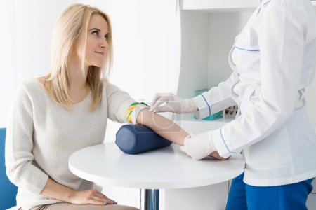 Photo for Preparation for blood test with beautiful young blond woman by female doctor in white coat medical uniform on the table in white bright room. Nurse rubbing a hand styryl patient tissue. - Royalty Free Image