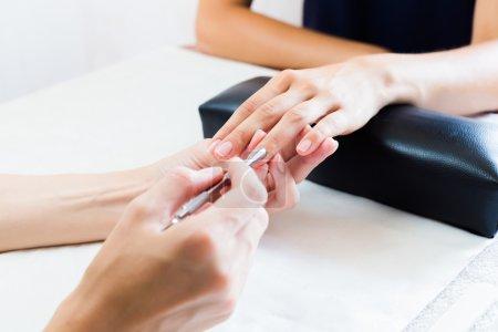 Photo pour Esthéticienne, faire une manucure dans un salon à une cuticule Mesdames repoussant pour renforcer l'ongle, bouchent avec vue sur les mains - image libre de droit