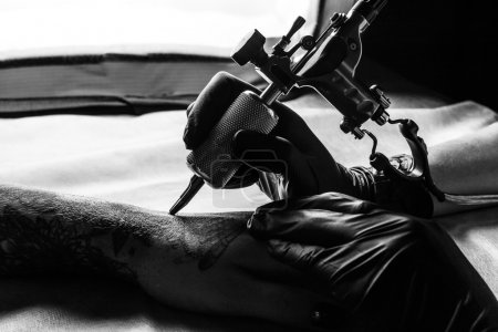 Close up picture of tattooist make a tattoo on clients arm in bw. Master works on the desk in black sterile gloves and hold a tattoo machine
