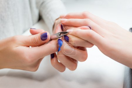 Finger nail care by manicure specialist in salon