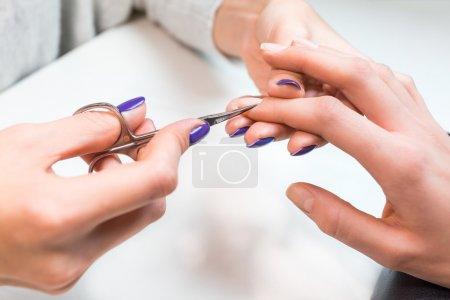 Manicure applying, cutting cuticle with scissors