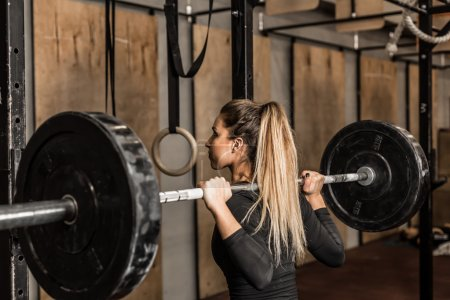 Photo for Closeup young and fit female athlete performed squats in the gym.Beautiful blonde girl during workout in gym with barbell on her shoulders - Royalty Free Image