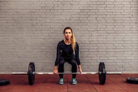 Girl athlete in starting position deadlift