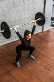 Woman training squats with barbells over head