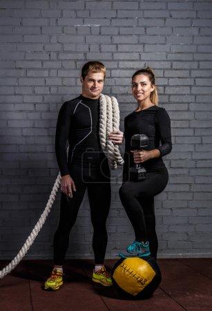Photo pour Homme fort tenant une femme sportive avec corde de sport tordue sur l'épaule et fille souriante avec haltère et mettre la jambe sur la balle - image libre de droit