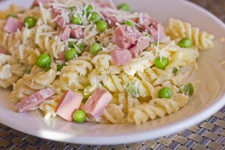 Photo pour Salade de pâtes au jambon et petits pois verts garnis de parmesan râpé - image libre de droit
