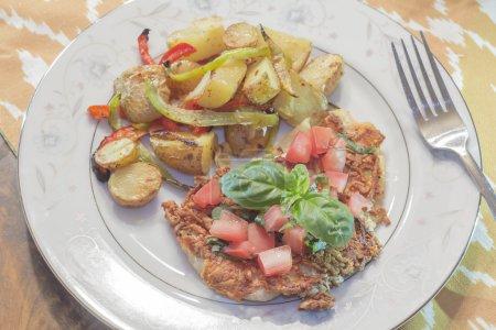Photo pour Poitrine de poulet croûtée au parmesan, saine mais farcie, garnie de tomates coupées en dés et de basilic frais et d'un côté de délicieux poivrons - image libre de droit