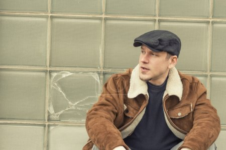 Cool guy in aviator jacket and newsie cap relaxes ...