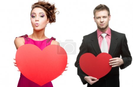 Young funny woman and handsome man holding red heart on white ba