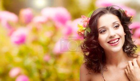 Photo pour Belle jeune femme avec des fleurs dans les cheveux sur fond automne - image libre de droit