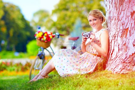 Photo for Woman after bicycle ride relaxing with camera - Royalty Free Image