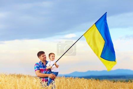 père et fils, agitant le drapeau ukrainien sur le champ de blé