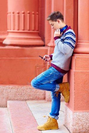 Stylish teenage boy listens to the music on smart phone