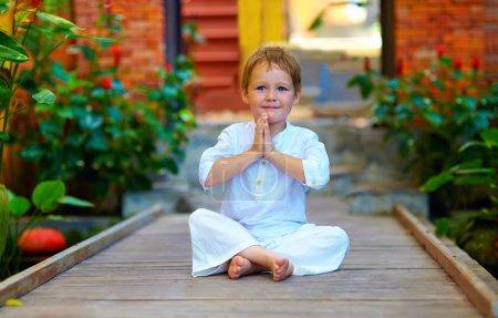 Photo pour Mignon garçon essayant de trouver l'équilibre intérieur en méditation - image libre de droit