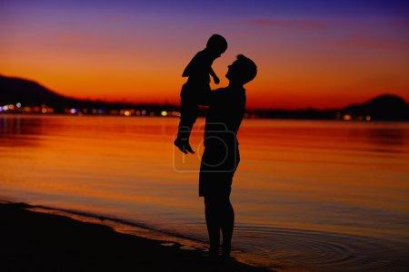 Photo pour Père et fils profiter de la vie au coucher du soleil - image libre de droit