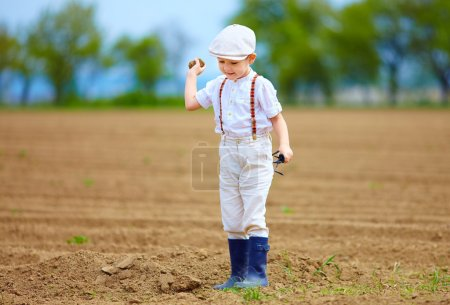 Photo for Cute little farmer on spring field, with earth clod in hand - Royalty Free Image