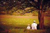 Otec a syn sedí pod stromem na jaře trávníku