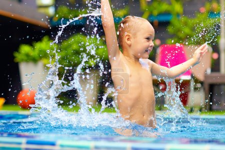 Photo for Excited happy kid boy jumping in pool, water fun - Royalty Free Image