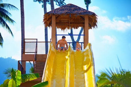 Photo for Happy father and son are ready to slide in tropical aqua park - Royalty Free Image