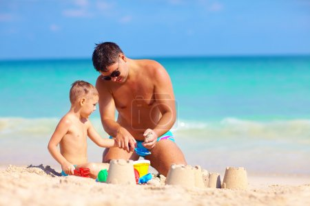 Photo for Father helps son build the sand castle on summer beach - Royalty Free Image