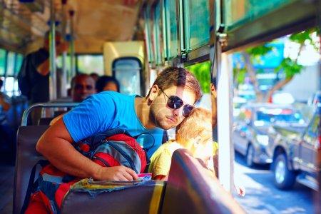 Vater und Sohn im öffentlichen Bus ohne Fenster durch asiatische Stadt
