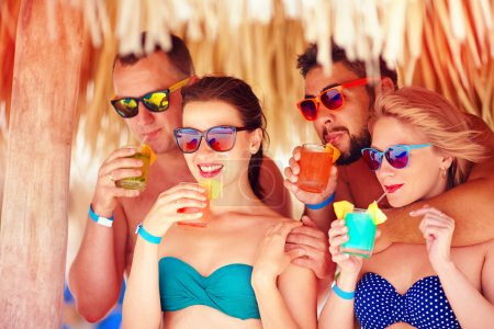 Photo for Group of happy friends having fun on tropical beach, drinking colorful cocktails - Royalty Free Image