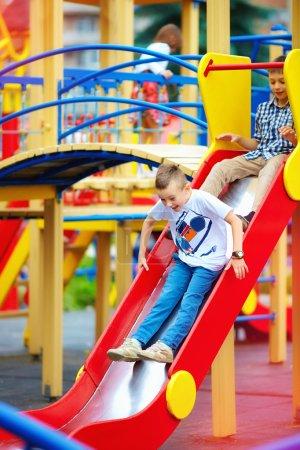 Photo pour Groupe d'enfants heureux glissant sur aire de jeux colorée - image libre de droit