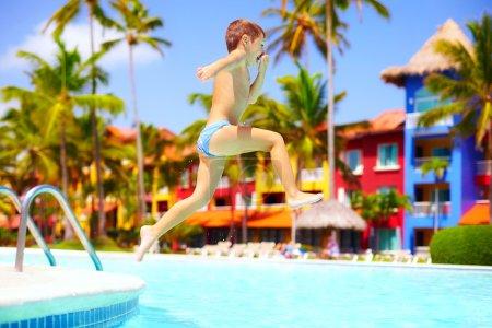 Photo pour Heureux enfant excité, sauter dans la piscine sur vacances d'été - image libre de droit
