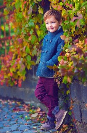 Photo pour Mignon garçon souriant posant près du mur coloré - image libre de droit