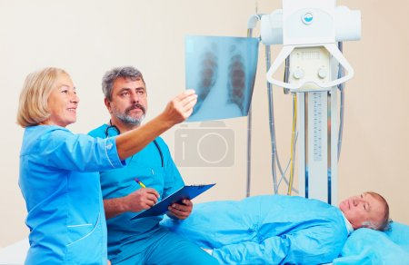 doctors discussing the roentgen radiogram in  X-ray room with patient