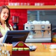 Young female cashier operating at the cash desk in...