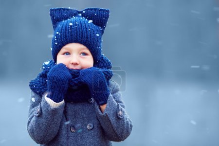 cute little boy, kid in winter clothes walking under the snow