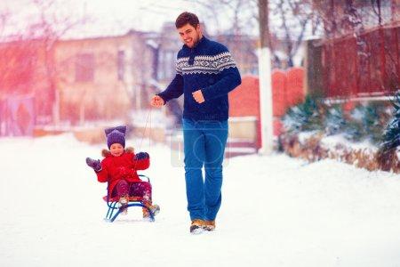 Photo pour Famille heureuse chevauchant le traîneau sous la neige d'hiver, sur la rue du village - image libre de droit