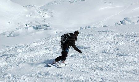 Photo pour Un snowboarder hors des sentiers sur un glacier dans la neige poudreuse - image libre de droit