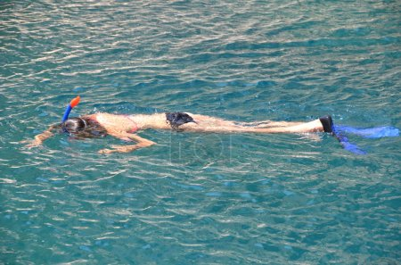 Girl snorkels in clear water