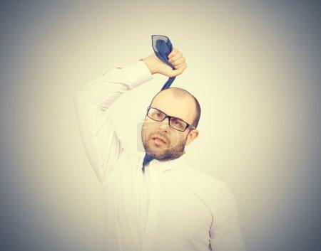 Suicidal businessman strangling himself tie