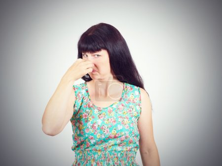 A young woman pinches the nose with fingers in disgust something stinks. bad smell, isolated. the expression of the human face. language of the body