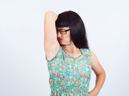 young woman, smelling, sniffing her wet armpit, something stink