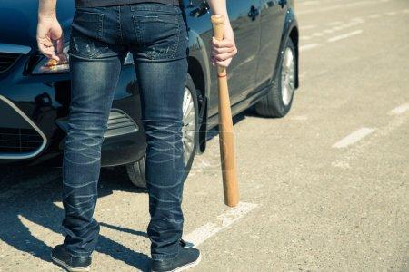 Photo pour L'homme avec une batte de baseball sur la route avant que la voiture - image libre de droit