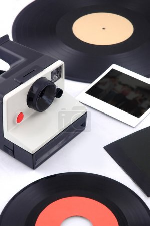 Old instant camera with vinyl and instant photos - eighties