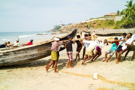 Fishermen pushing the fishing boat on the beach out of the Arabi