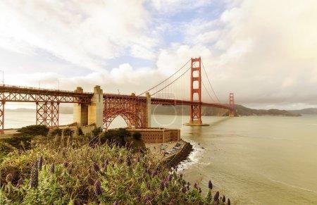Photo pour Le célèbre Golden Gate Bridge de San Francisco en Californie, États-Unis d'Amérique. Une vue sur Fort Point, la baie, les surfeurs et le pont suspendu rouge reliant Frisco au comté de Marin au coucher du soleil . - image libre de droit