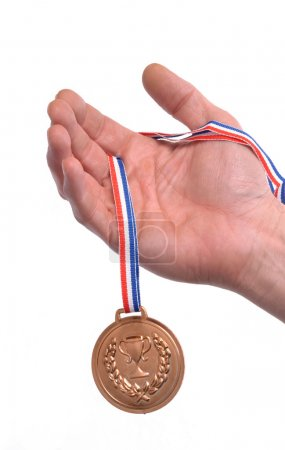 Hand holding a gold medal