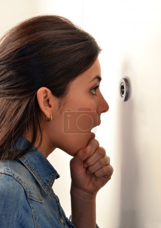 Woman looking out through the peephole