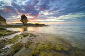 Moss rock with sunset background at Batu Payung (Umbrella Beach) at Lombok, Indonesia