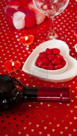 Photo pour Saint Valentin. Bouteille de vigne, verres, roses rouges, bougies - fond rouge. Concept de dîner d'amour - Photo verticale - image libre de droit